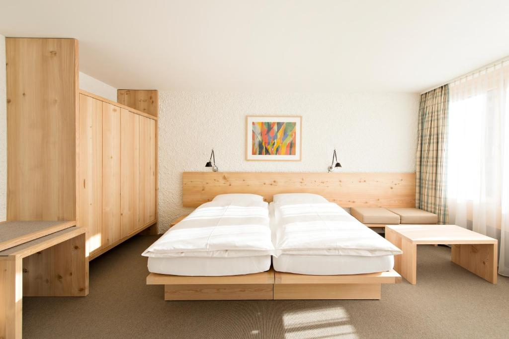 A bed or beds in a room at Hauser Hotel St. Moritz