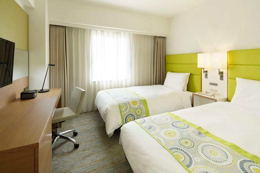A bed or beds in a room at ANA Holiday Inn Sapporo Susukino