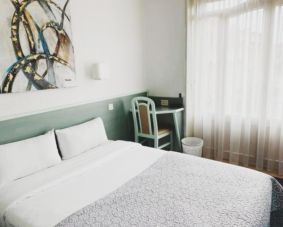 A bed or beds in a room at Hôtel Escurial