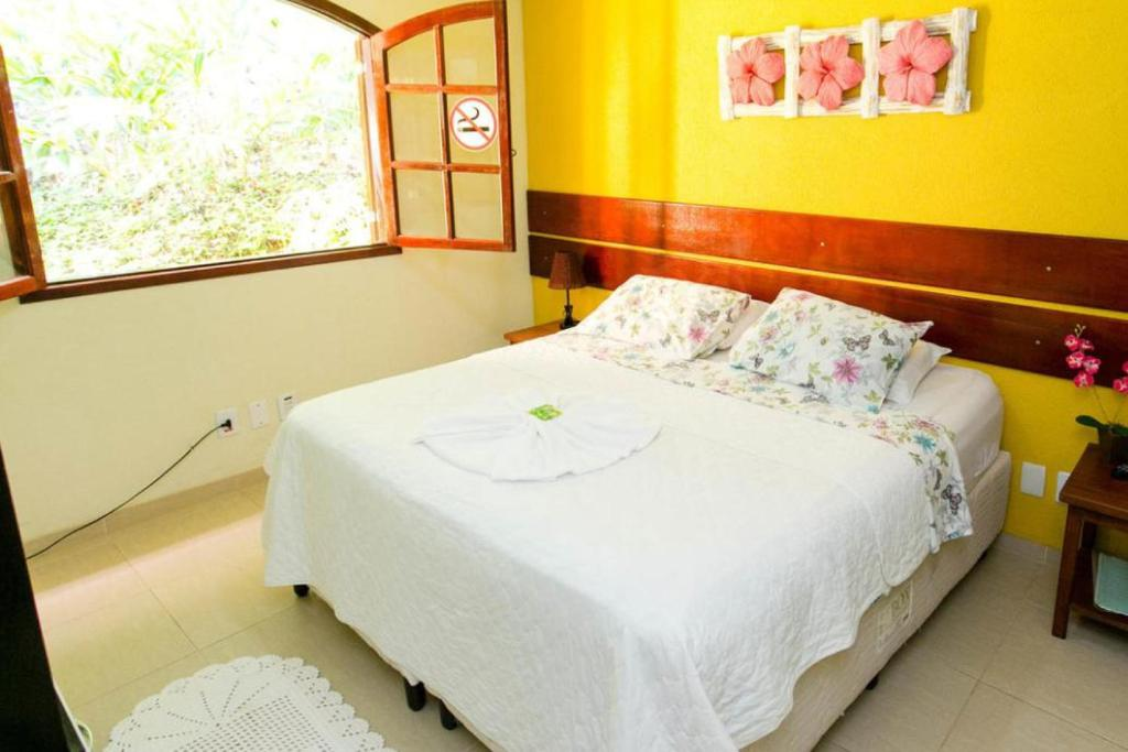 A bed or beds in a room at Pousada Rio Bracuhy