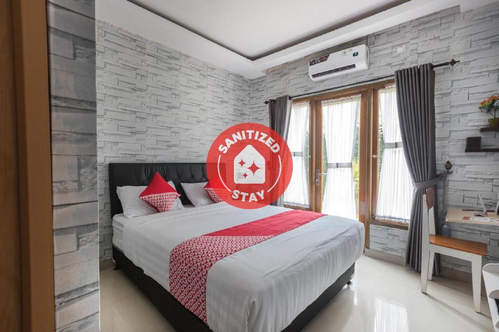 A bed or beds in a room at OYO 1769 Mahayun Guest House Syariah