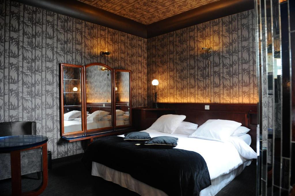 Een bed of bedden in een kamer bij Le Berger Hotel