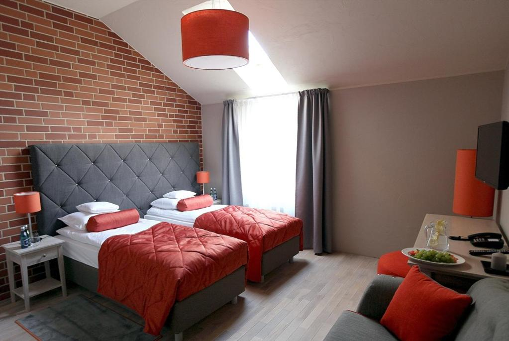 A bed or beds in a room at Hotel Browar Kościerzyna
