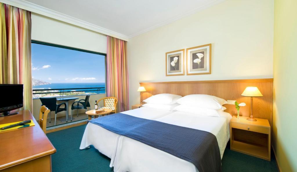 Ein Bett oder Betten in einem Zimmer der Unterkunft Madeira Panorâmico Hotel
