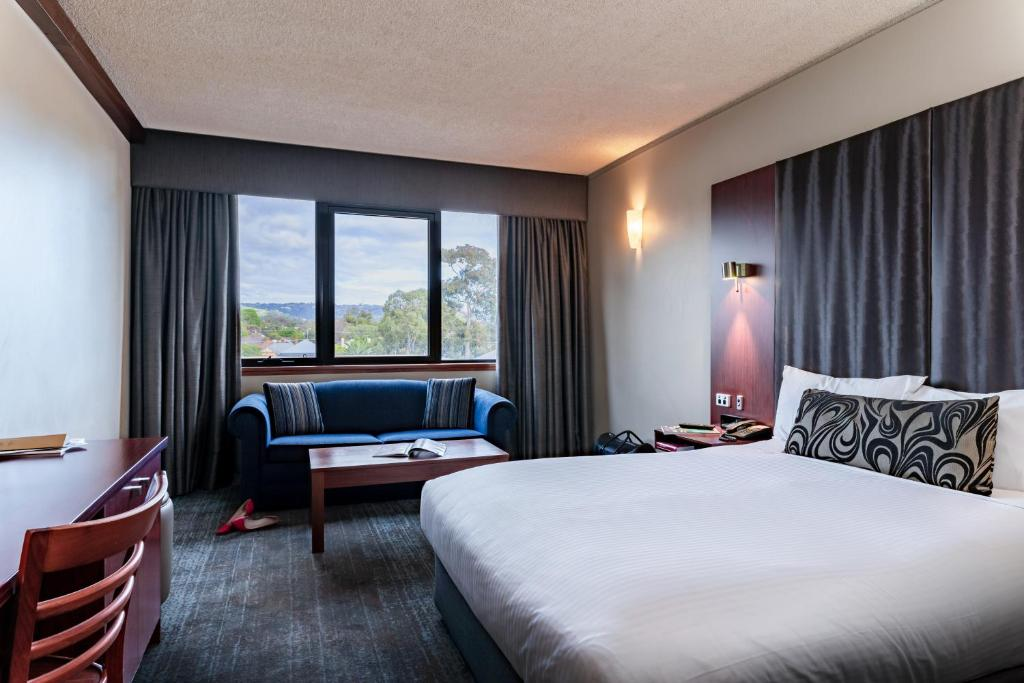 A bed or beds in a room at Arkaba Hotel