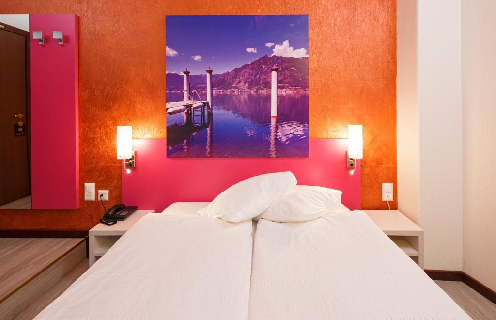 A bed or beds in a room at Acquarello Swiss Quality Hotel