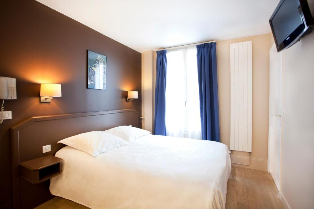 A bed or beds in a room at Nadaud Hotel