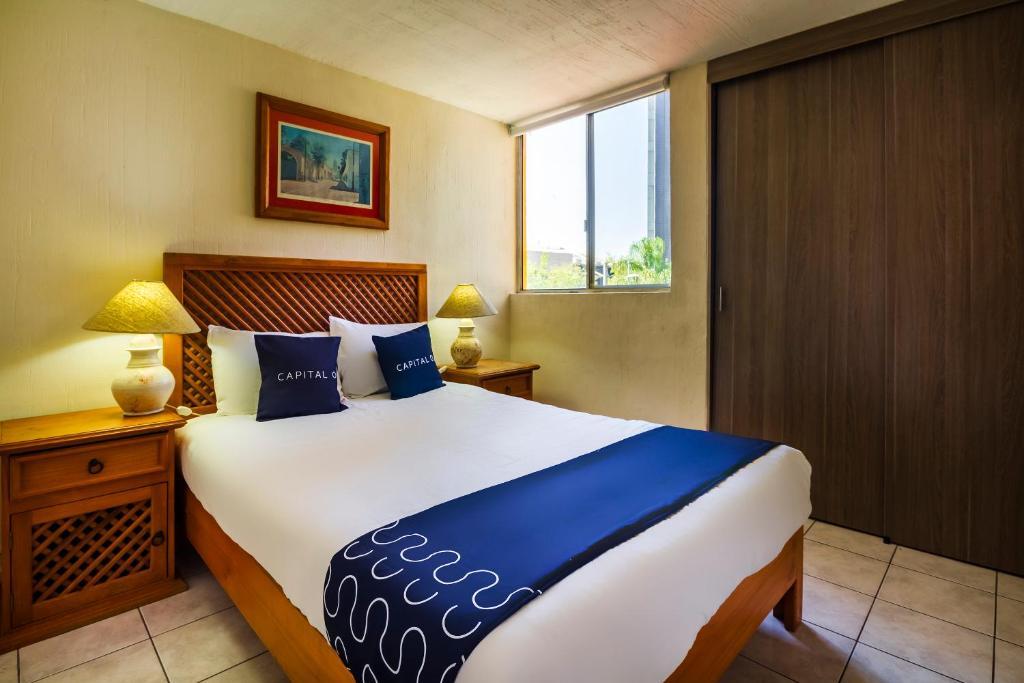Cama o camas de una habitación en Capital O Suites Navata