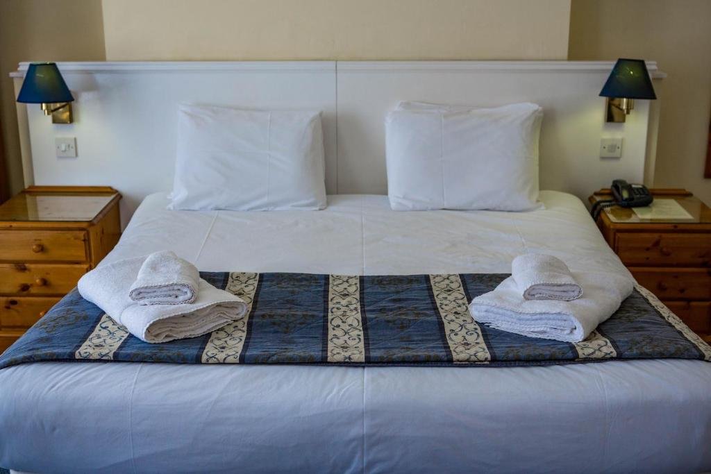 A bed or beds in a room at Yelf's Hotel
