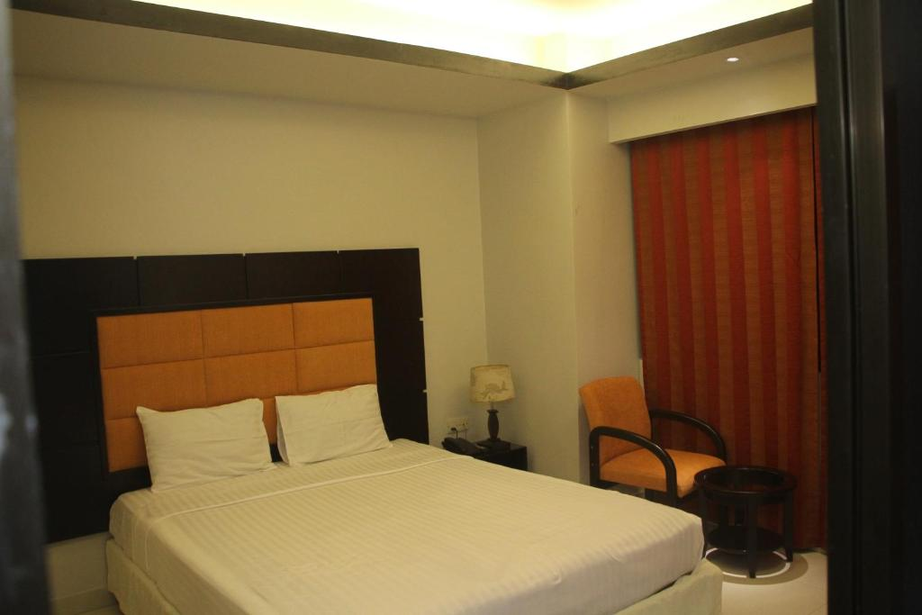 A bed or beds in a room at Orchid Business Hotel