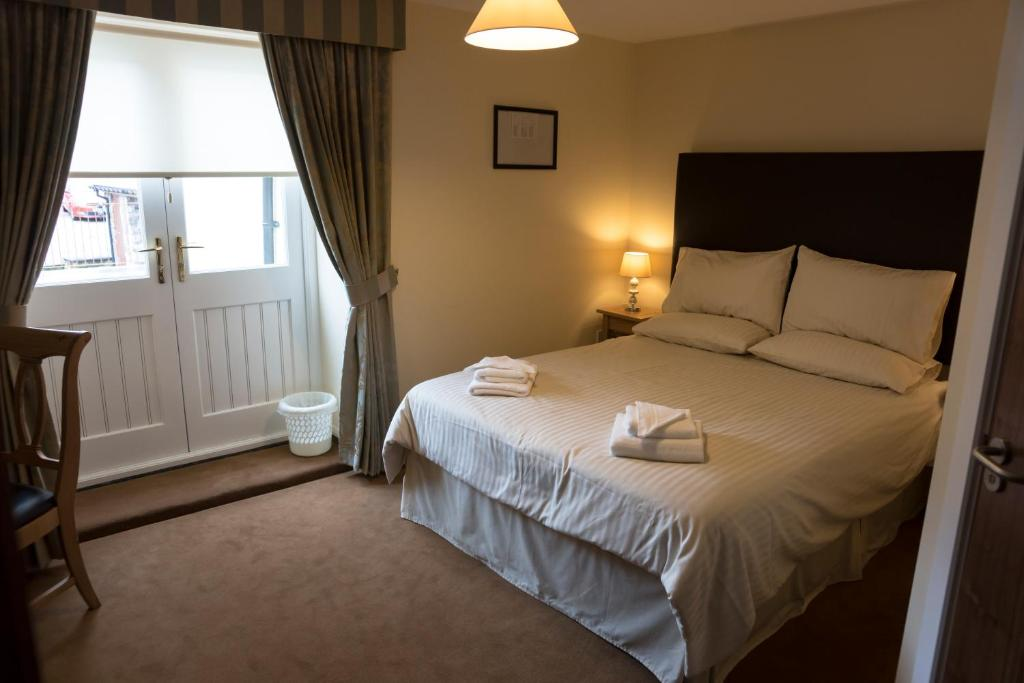 A bed or beds in a room at Cambrian Inn