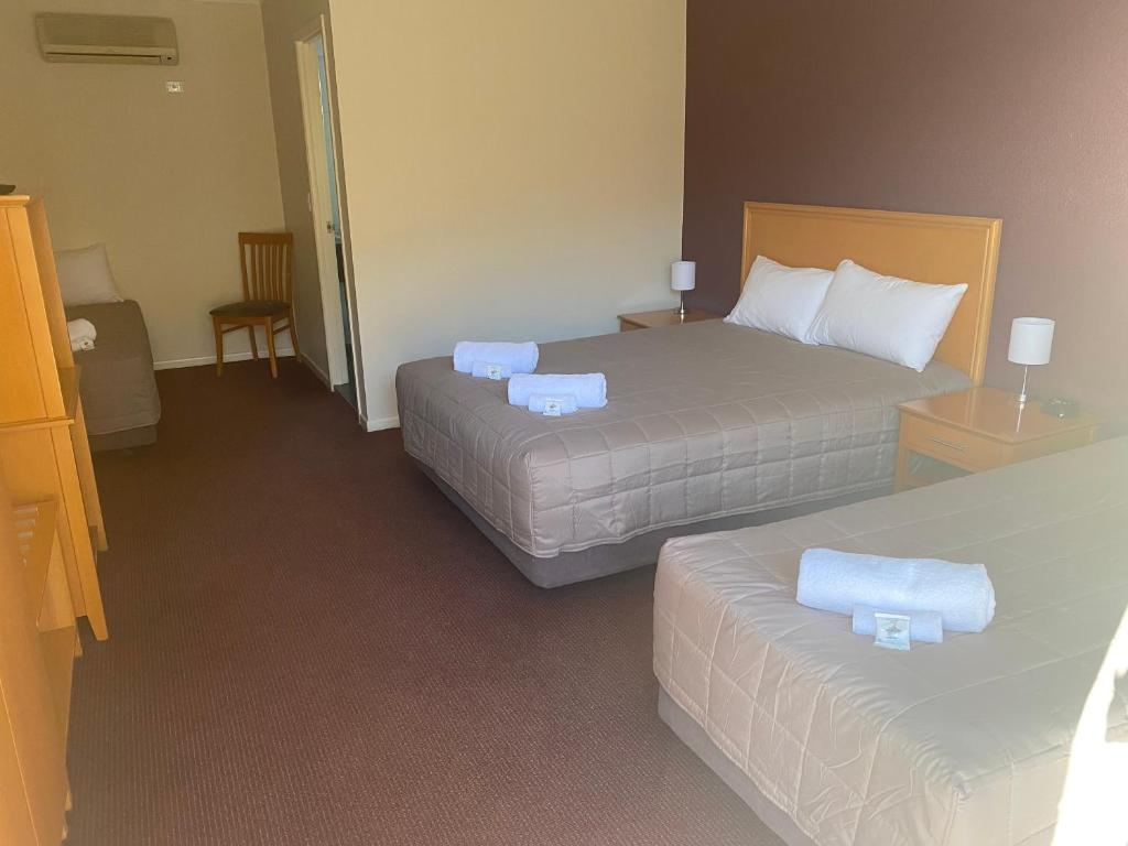A bed or beds in a room at Horse & Jockey Hotel Motel
