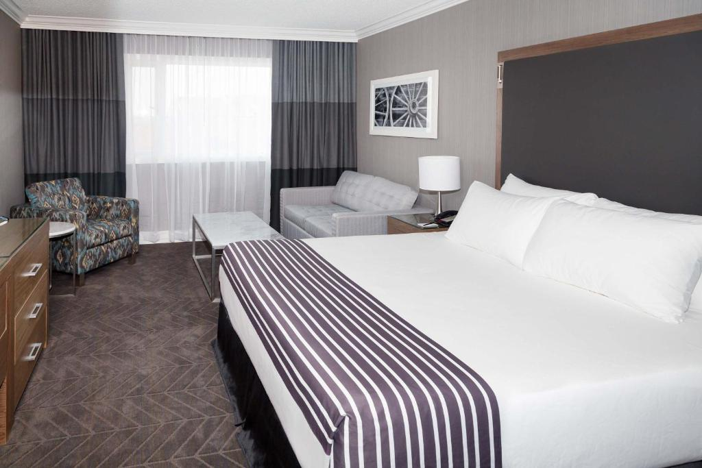 A bed or beds in a room at Sandman Signature Lethbridge Lodge