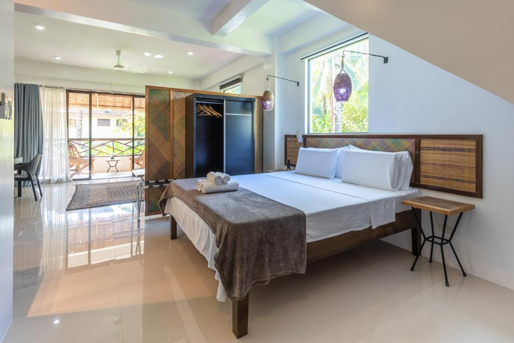 A bed or beds in a room at Kalipay Resort Siargao