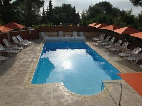 Vue sur la piscine de l'établissement Hôtel Les Amandiers ou sur une piscine à proximité