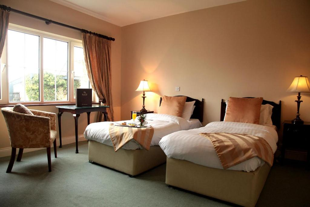 A bed or beds in a room at Springfort Hall Hotel