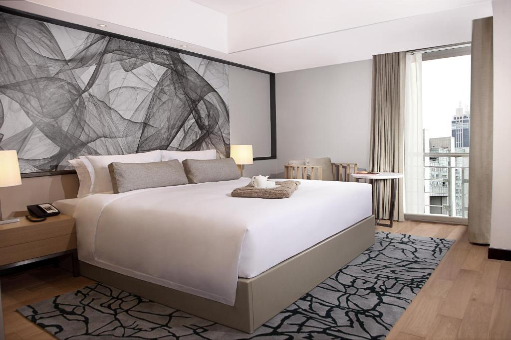 A bed or beds in a room at Riverdale Residence Xintiandi Shanghai 长河国际公寓新天地