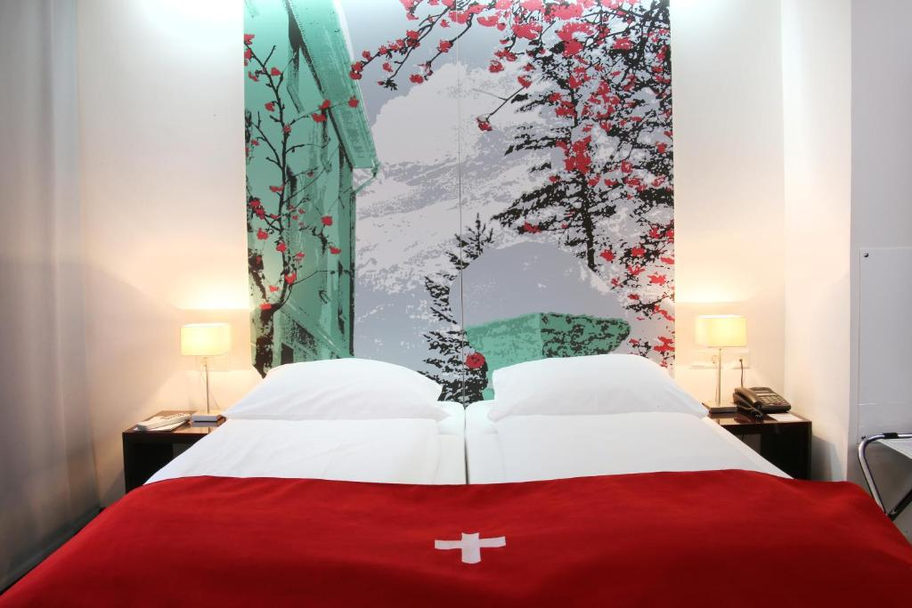 A bed or beds in a room at Helvetia Hotel Munich City Center
