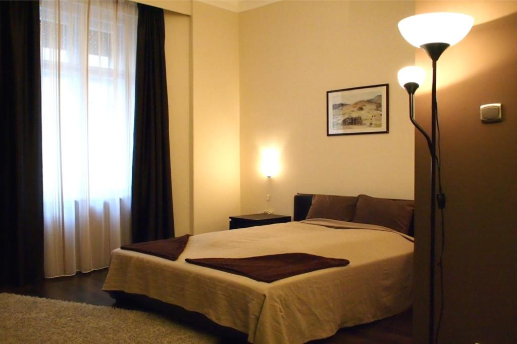 A bed or beds in a room at Budapest Suites