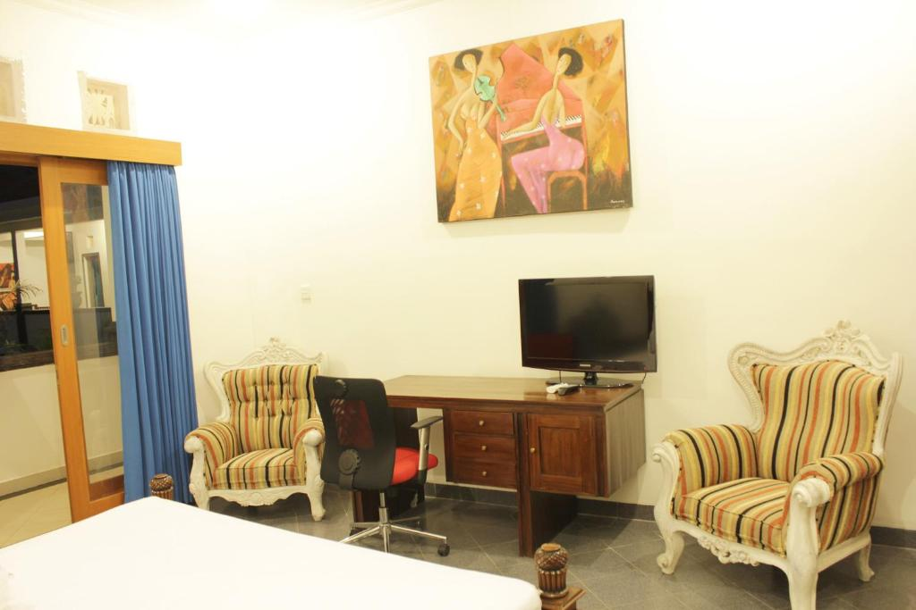 A television and/or entertainment centre at Ayu Guest House