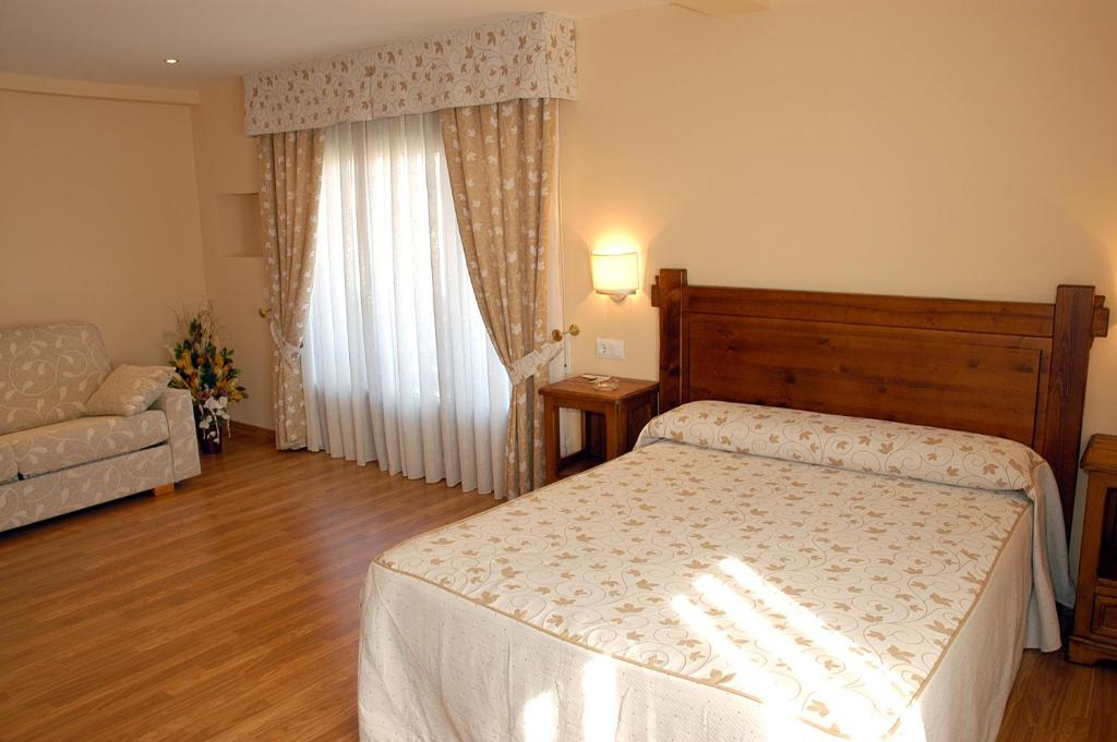 A bed or beds in a room at Aparthotel Tres Caminos