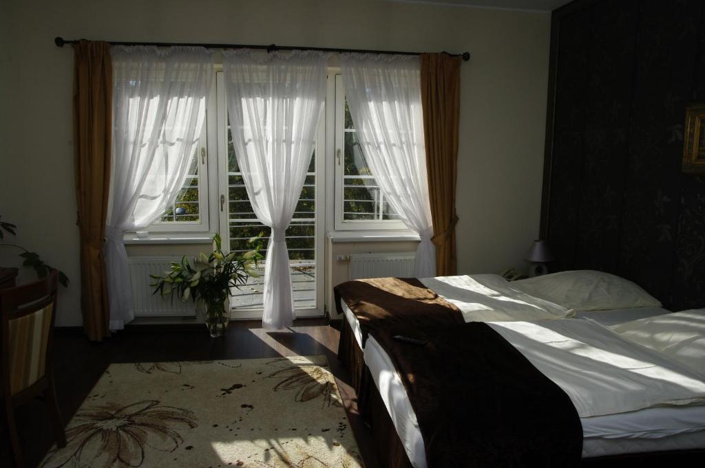 Łóżko lub łóżka w pokoju w obiekcie Pensjonat - Restauracja Żółty Domek