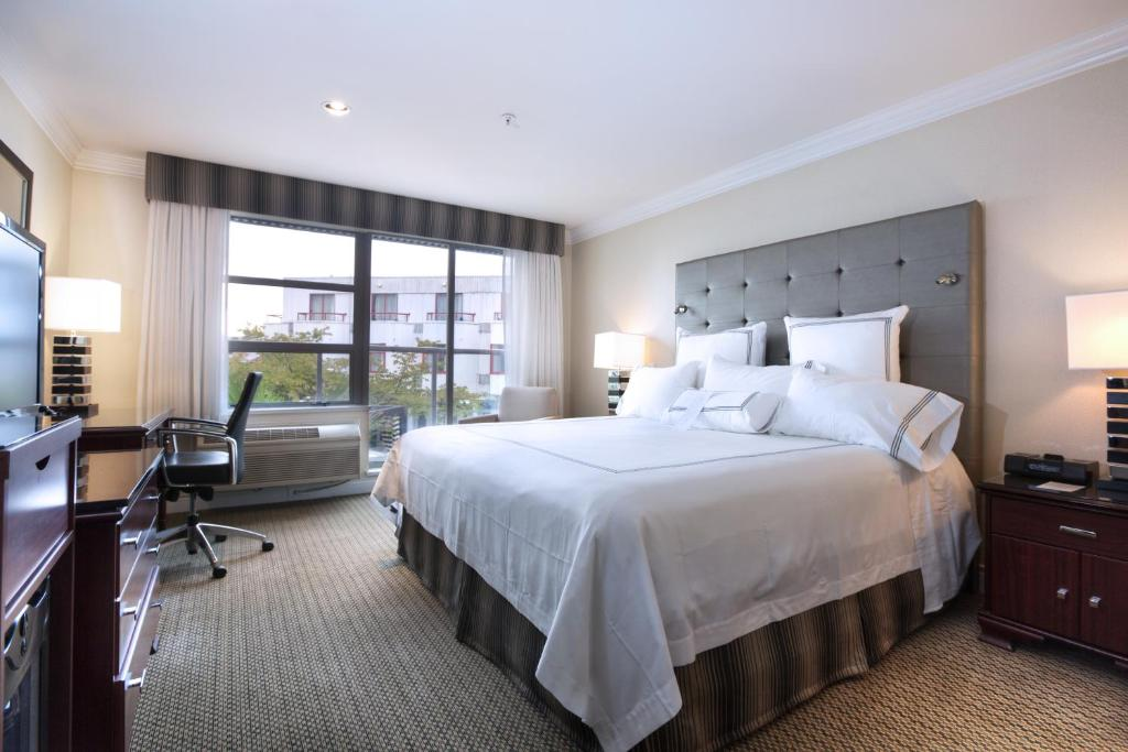 A bed or beds in a room at Granville Island Hotel
