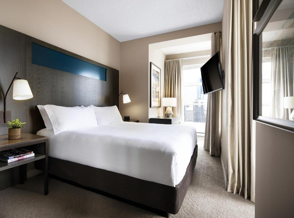 A bed or beds in a room at One King West Hotel and Residence