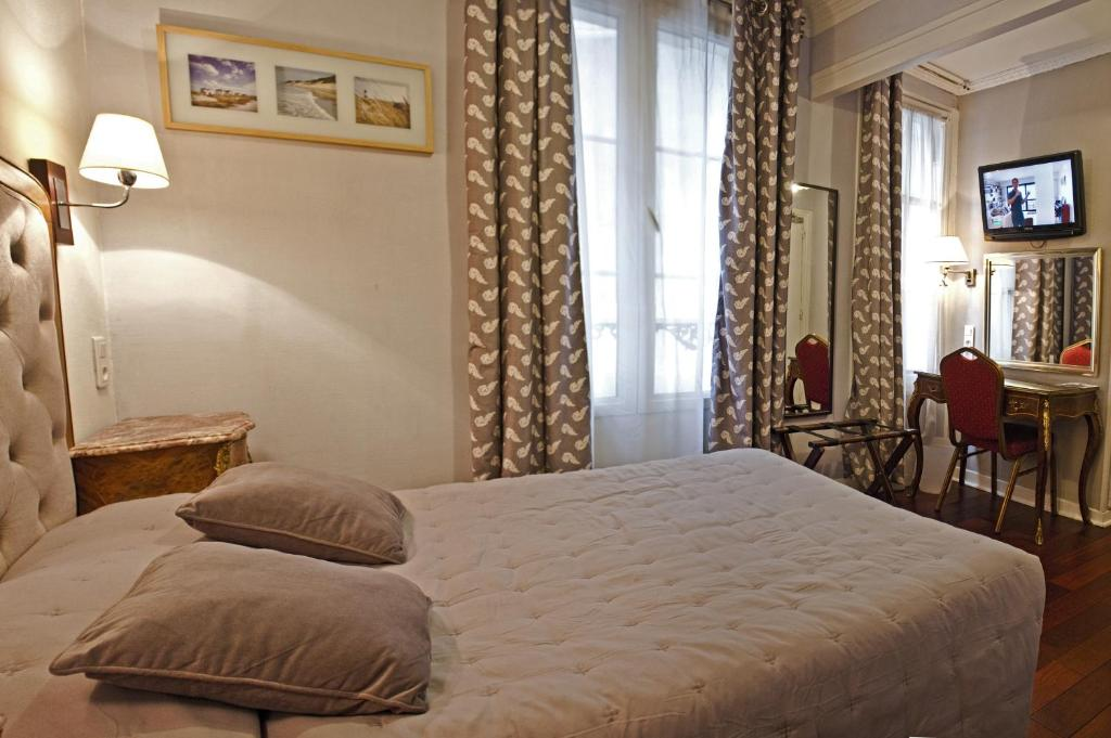 A bed or beds in a room at Hotel Hippodrome