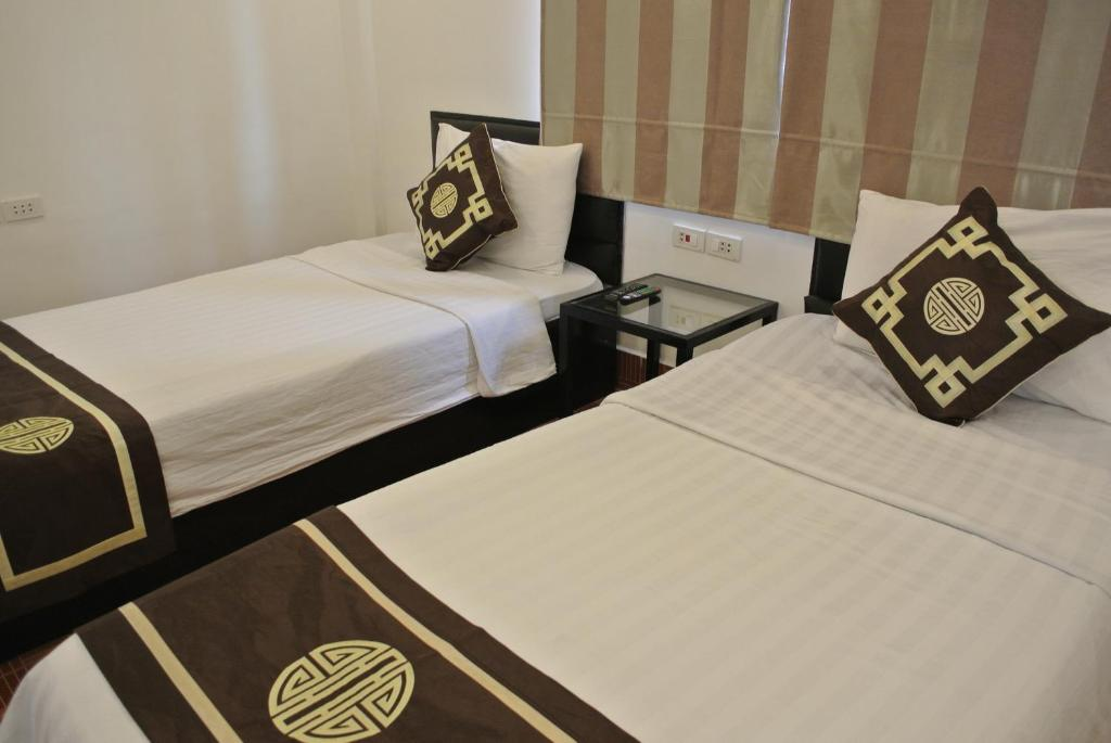 A bed or beds in a room at Vangvieng Boutique Hotel