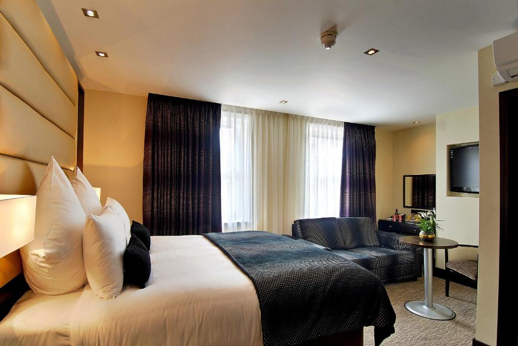 A bed or beds in a room at The Marble Arch Suites