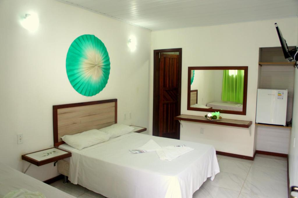 A bed or beds in a room at Pousada Camburi
