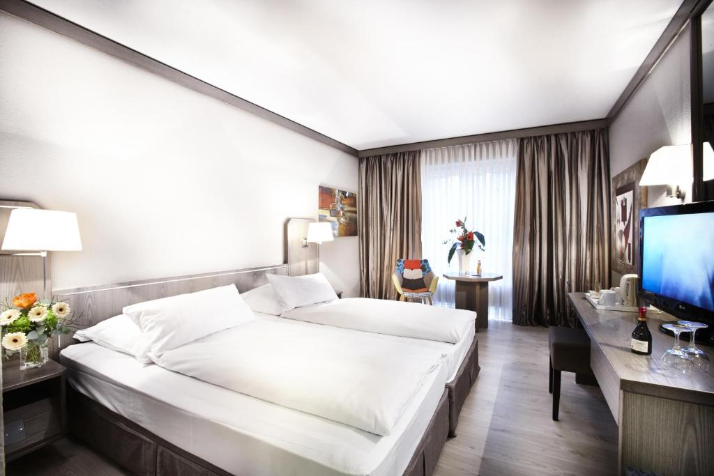 A bed or beds in a room at Hotel Düsseldorf City by Tulip Inn