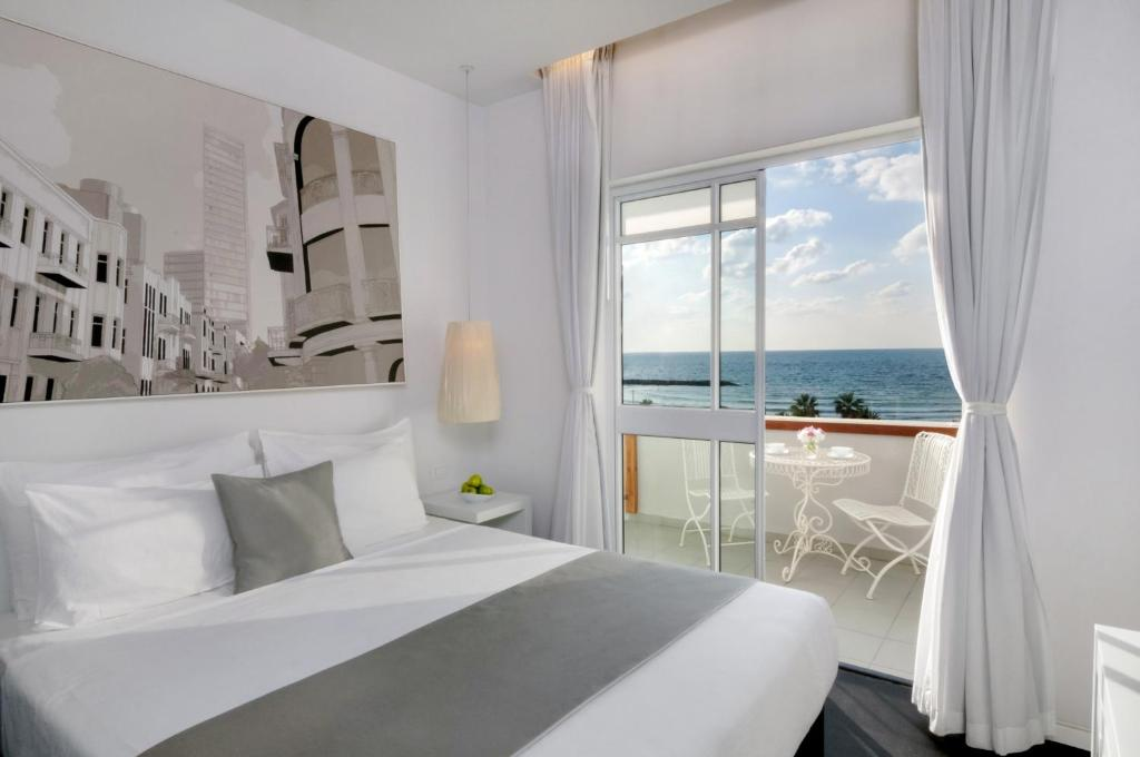 A bed or beds in a room at Olive Gordon By The Beach