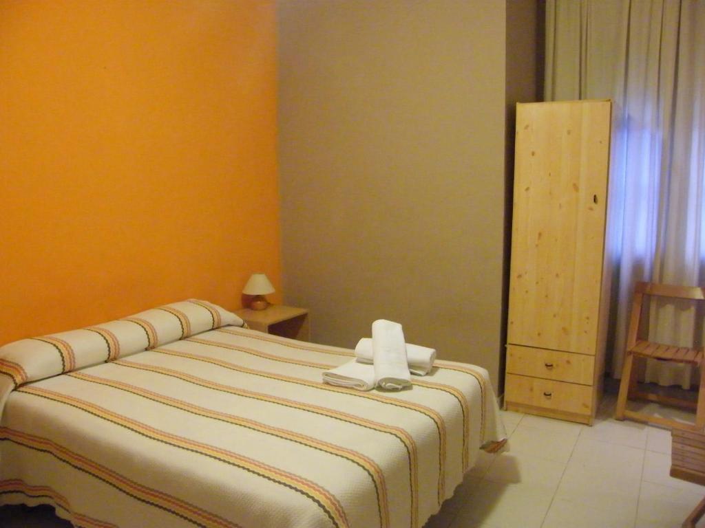 A bed or beds in a room at Pensión Corona