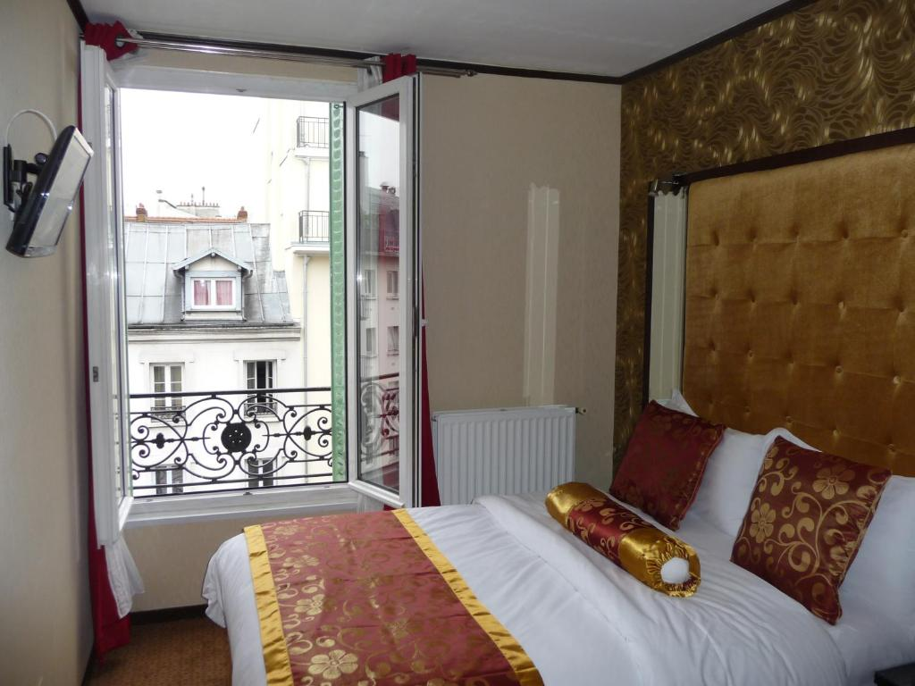 A bed or beds in a room at Hôtel des Buttes Chaumont