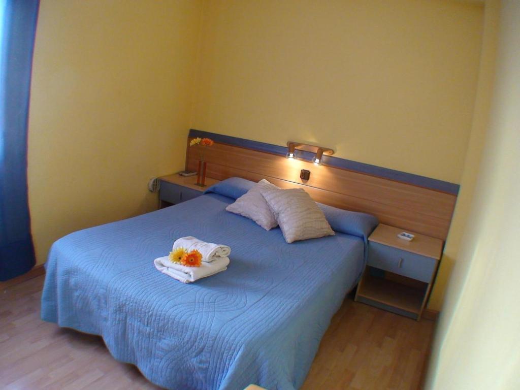 A bed or beds in a room at Hostal El Carmen