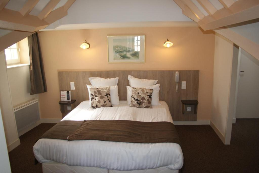 A bed or beds in a room at La Vieille Auberge