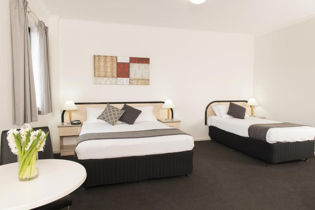 A bed or beds in a room at Adelaide Riviera Hotel