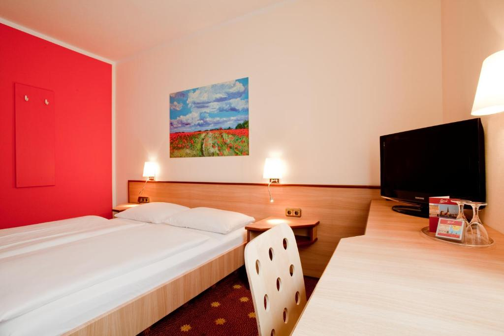 A bed or beds in a room at Hotel die kleine Sonne Rostock
