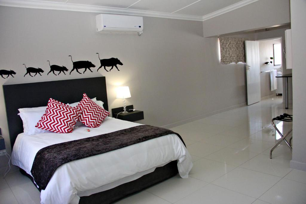 A bed or beds in a room at Green Kalahari Guesthouse
