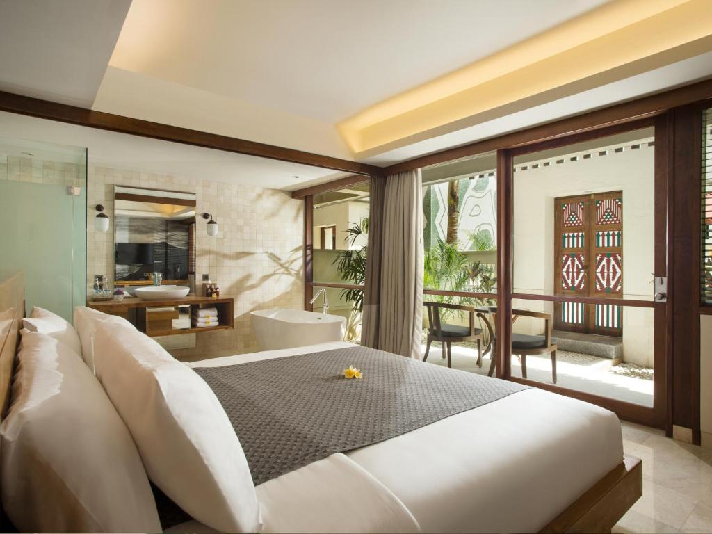 A bed or beds in a room at Amnaya Resort Kuta