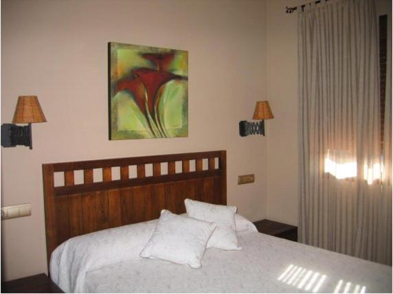 A bed or beds in a room at Hotel Rural Robles