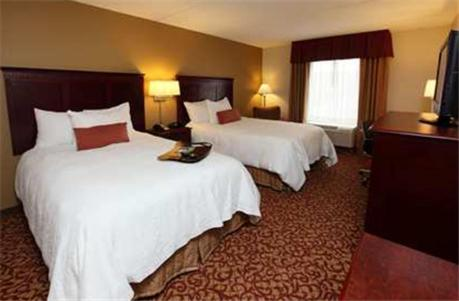 A bed or beds in a room at Hampton Inn & Suites Charlottesville at the University
