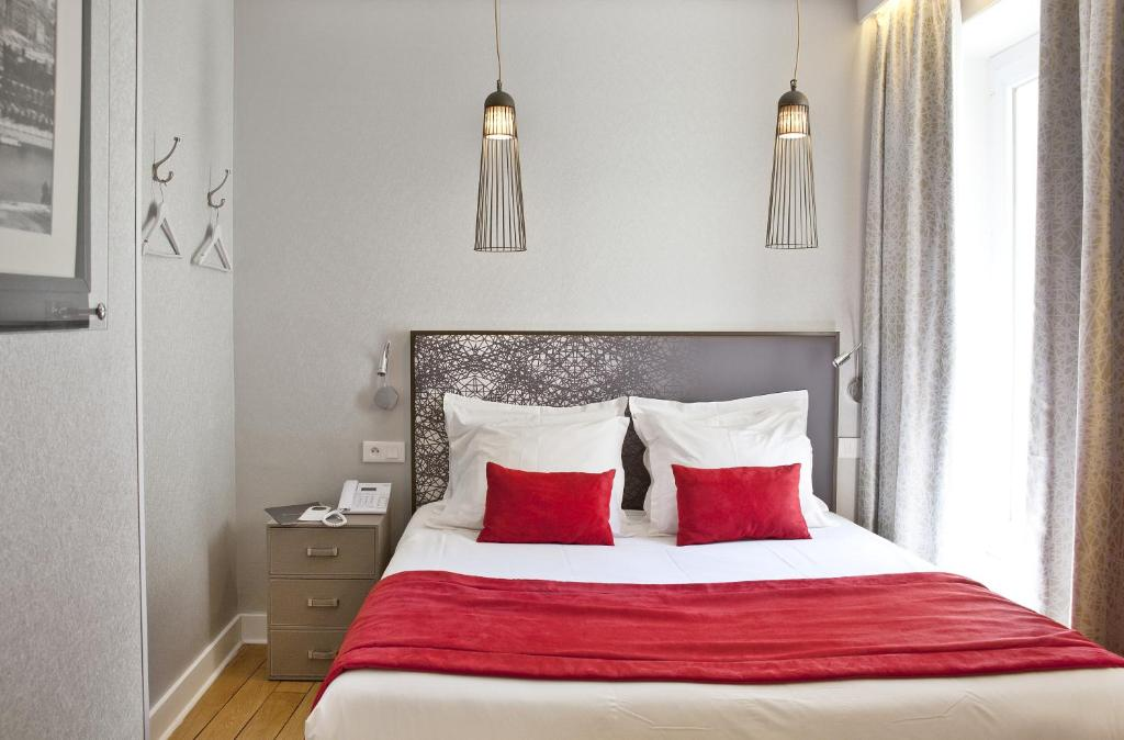 A bed or beds in a room at Hotel Eiffel Segur