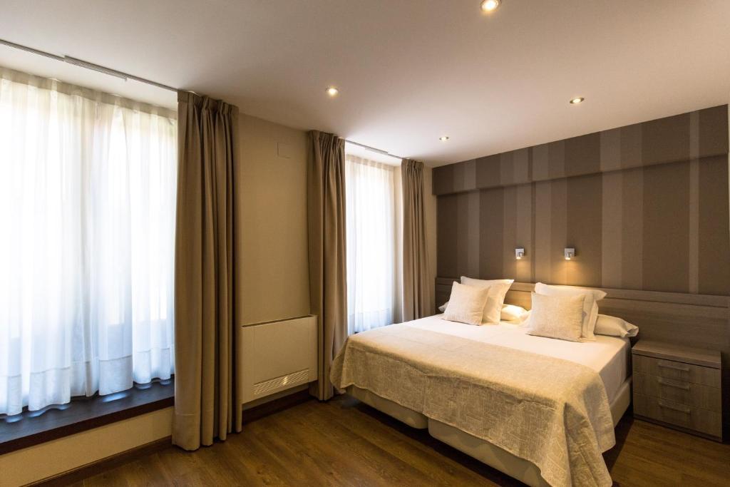 A bed or beds in a room at Apartamentos Turísticos Llanes