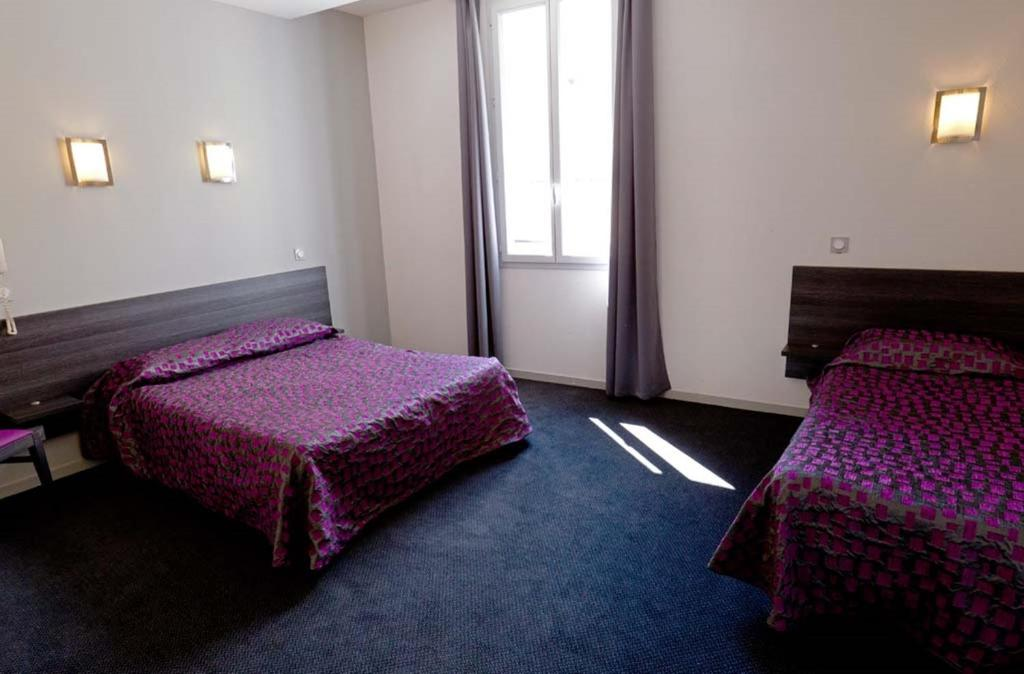 A bed or beds in a room at Hôtel Saint Etienne