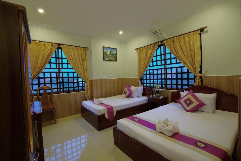 A bed or beds in a room at Serkirin Mary Angkor Villa