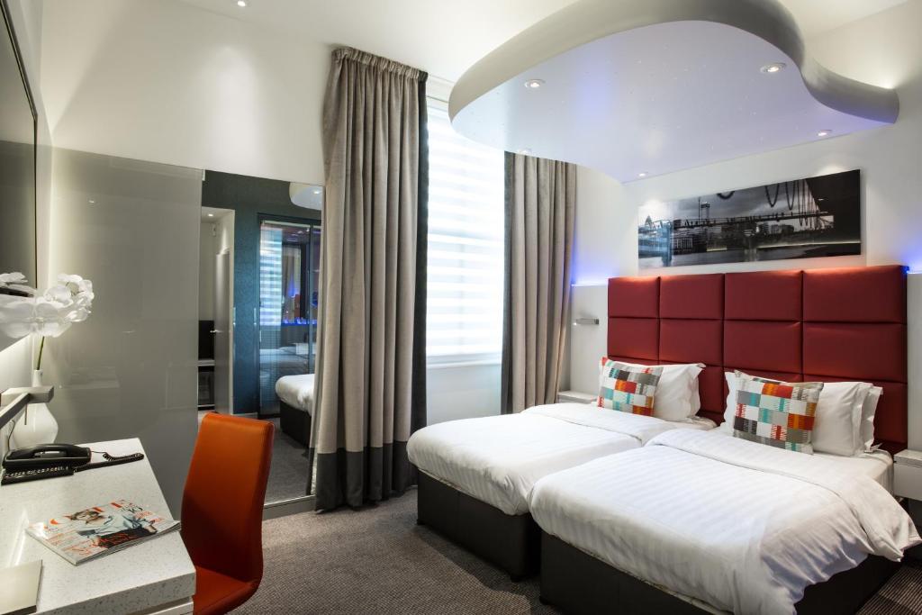 Säng eller sängar i ett rum på Henley House Hotel