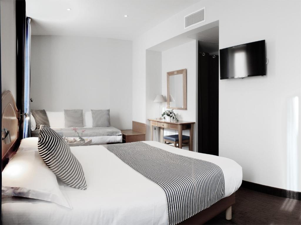 A bed or beds in a room at Hôtel Esprit d'Azur